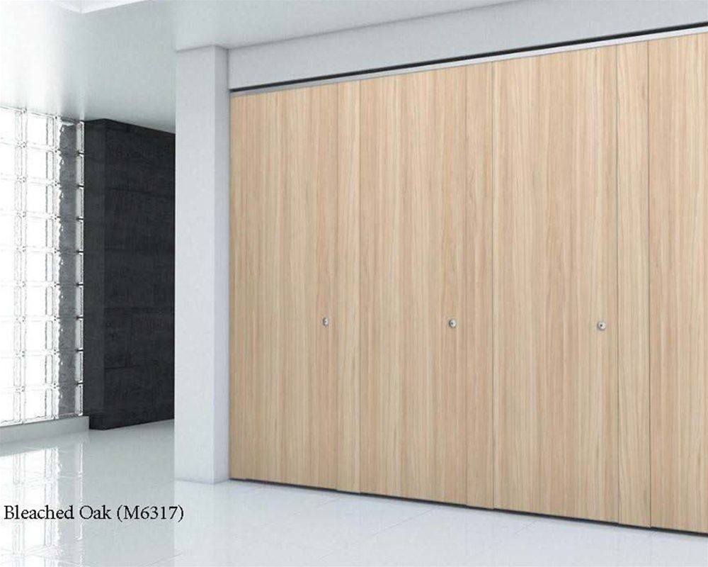 Bleached oak toilet cubicle doors that are full length and in a white furnished room
