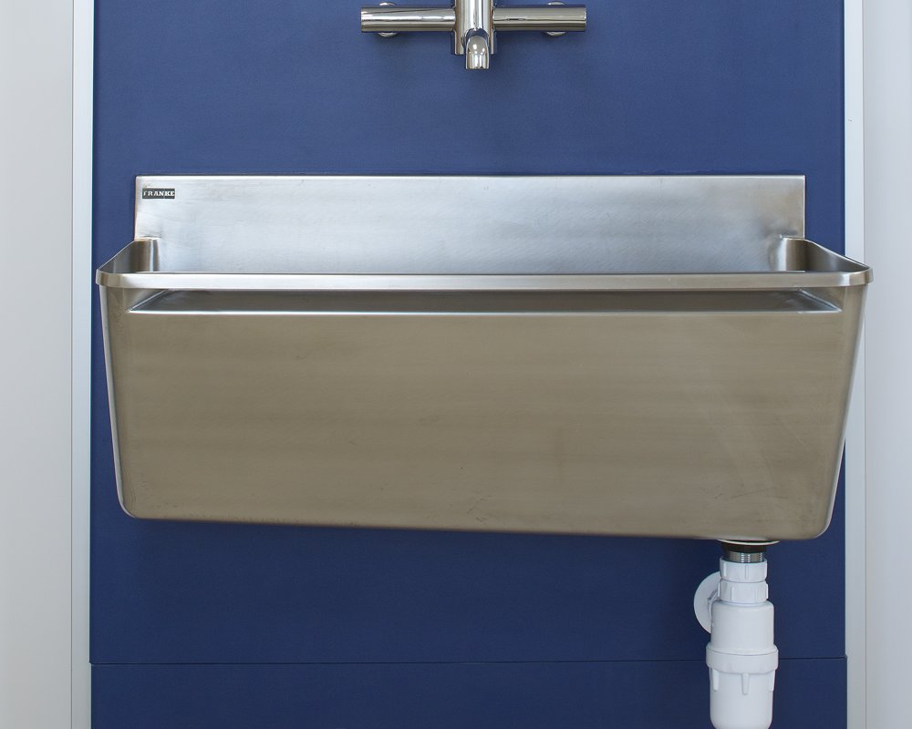 Stainless steel surgical scrup up trough and tap pre-plumbed on blue IPS panels.