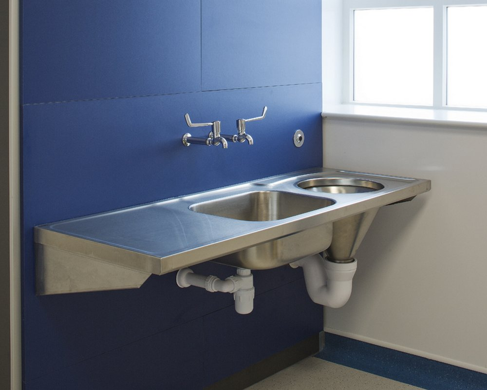 Stainless steel clinical disposal unit, sink and taps pre-plumbed on blue IPS panels