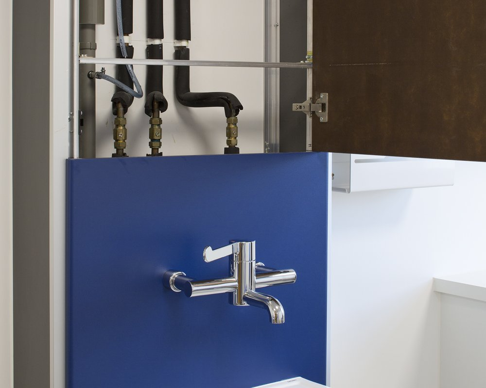 Blue healthcare boxed out unit with top panel open showing plumbing