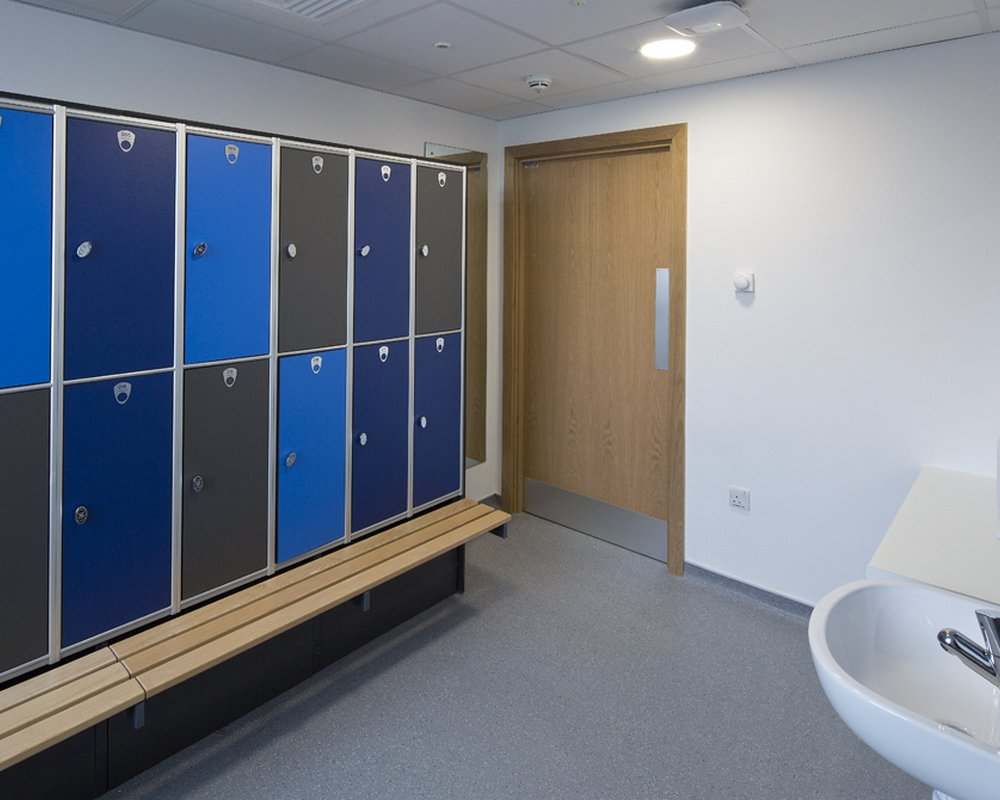 Blue and grey lockers and ash locker benching in staff area at Acre Mills Hospital