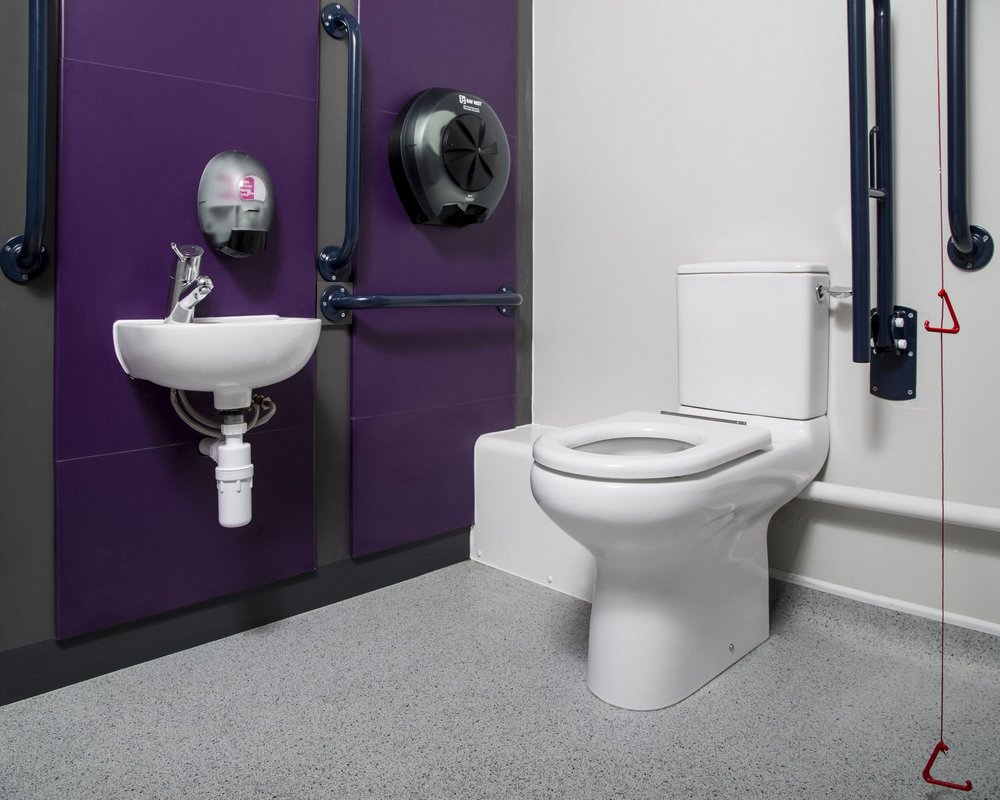 Huddersfield University Doc M accessible toilet with WC, basin and grabrails on purple panels