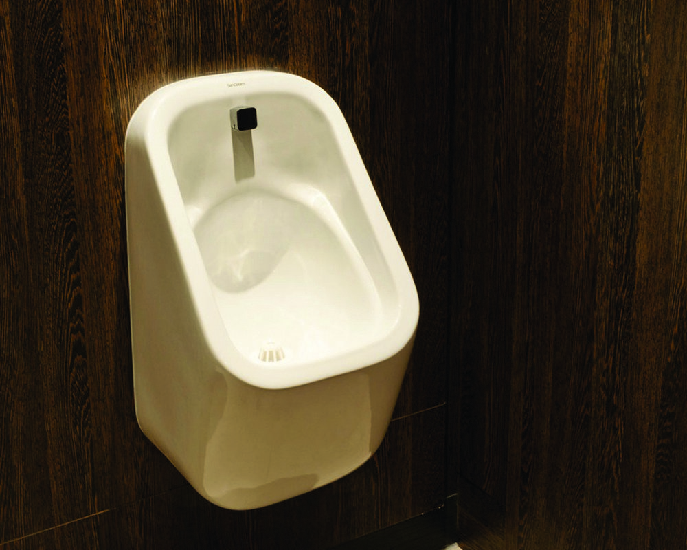 Ready plumbed wall hung White Marden Urinal with concealed cistern and trap behind duct shown in 'American Walnut'