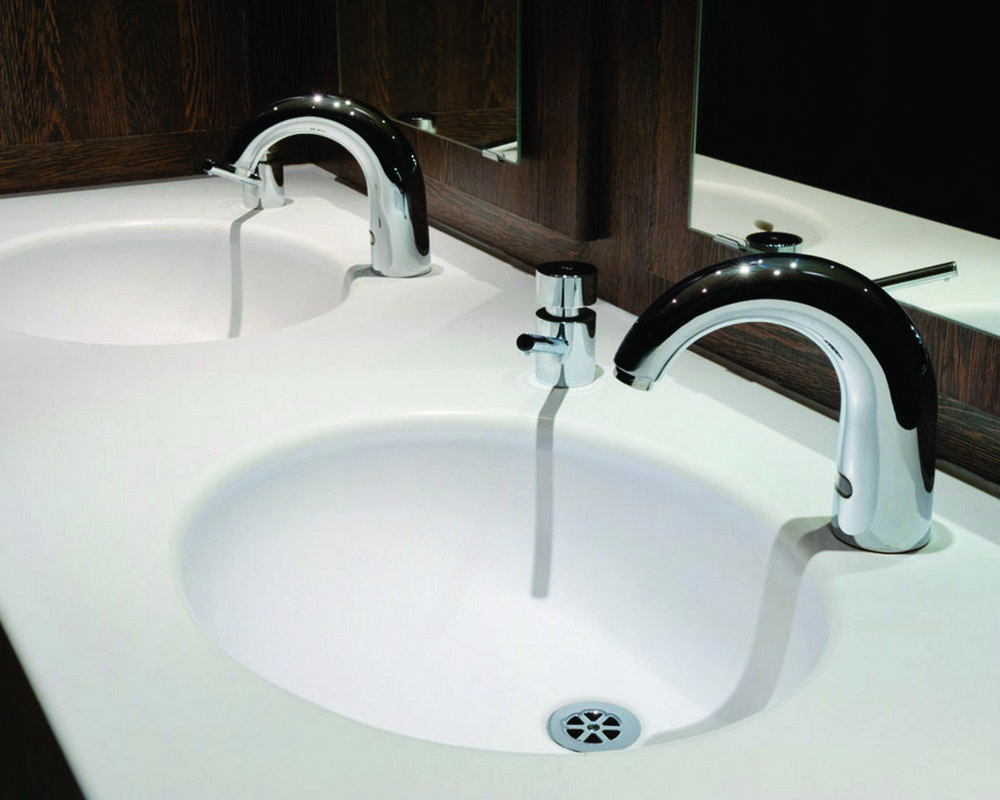 Integral Solid Surface basin in white 'Elysian' with sensor mixer tap and chrome soap dispenser and grid waste