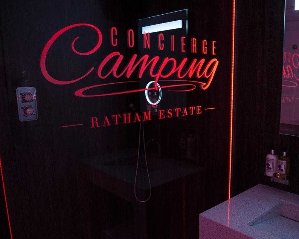 Concierge Camping branded shower screen lit up in the dark