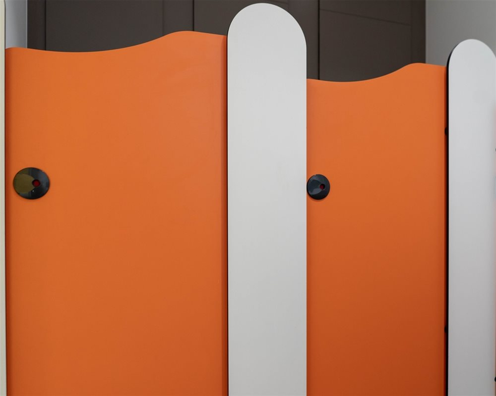 Tiny Stuff lower height toilet cubicles in 'Tangerine' orange and 'Arctic' white