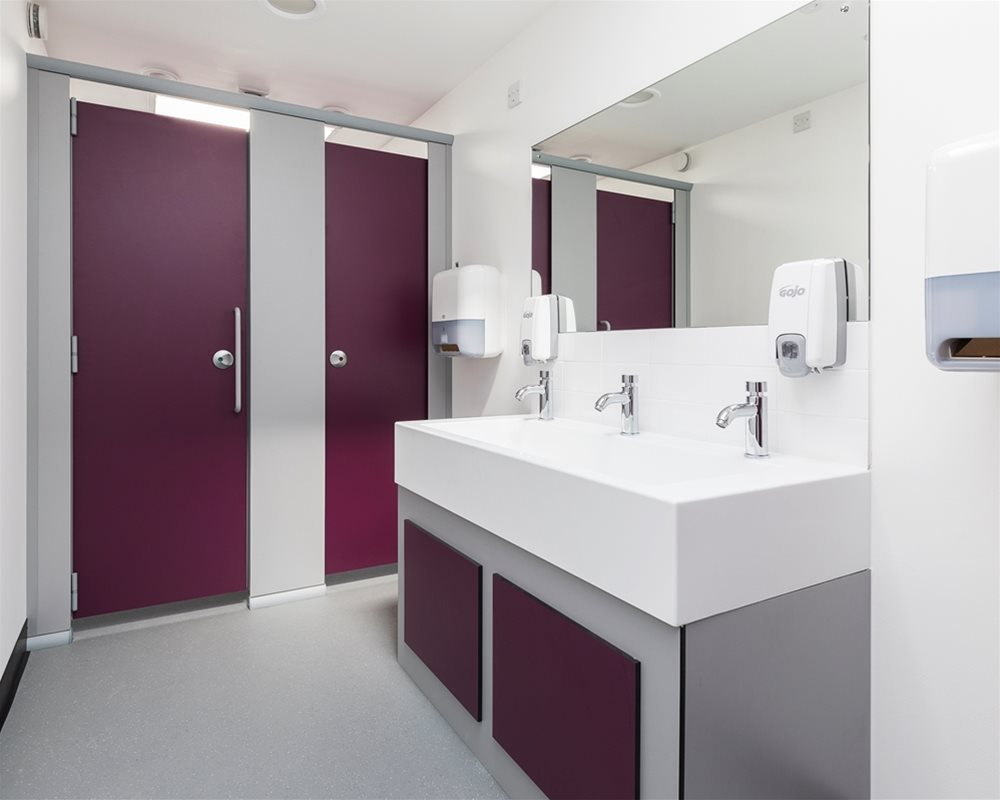 Quadro toilet cubicles in 'Mulberry' purple and 'Elysian' white Solid Surface Washtroughs for Norwich High School