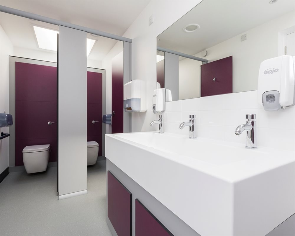 Washroom with open toilet cubicles and Marden wall hung white toilets on 'Mulberry' purple panel