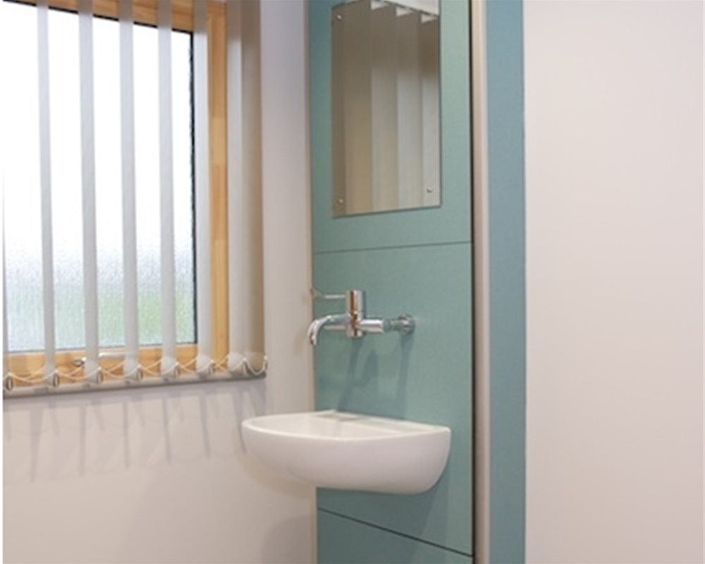 Traditional boxed out healthcare unit in 'Bay Leaf' green with SanCeram basin and tap