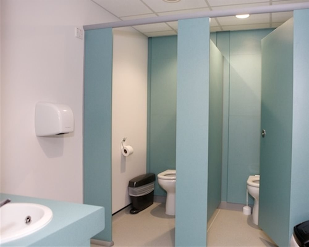 Quadro toilet cubicles in 'Bay Leaf' green and Chartham back to wall WCs